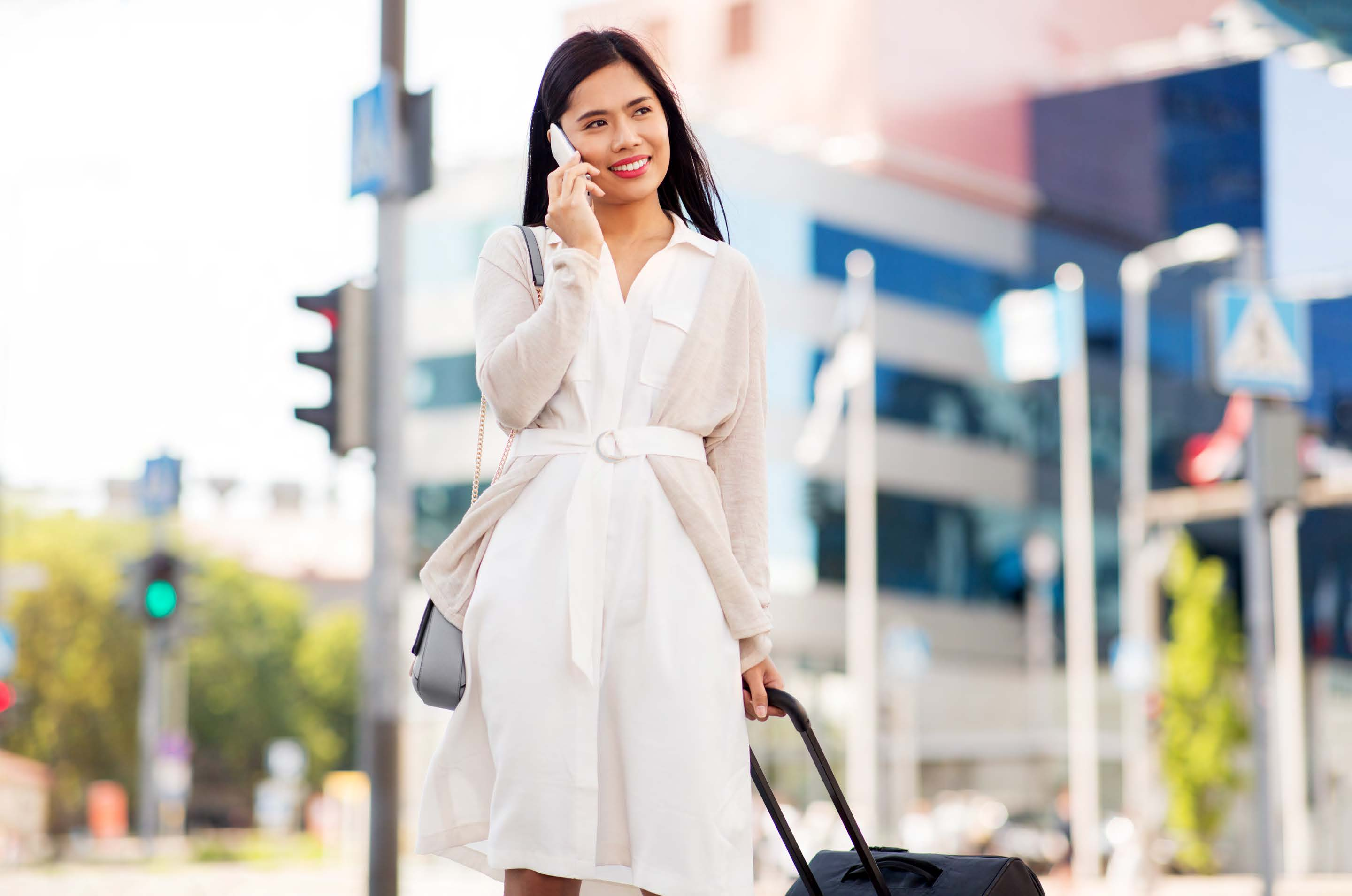 expatriate woman walking with suitcase and talking on cell phone